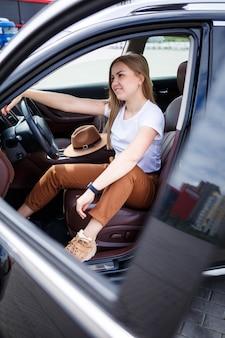 Een mooi meisje van europees uiterlijk met een bril en een bruine hoed staat in de buurt van een zwarte auto. jonge vrouw met auto in parking