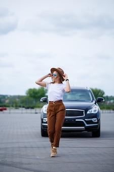 Een mooi meisje van europees uiterlijk met een bril en een bruine hoed staat in de buurt van een zwarte auto.
