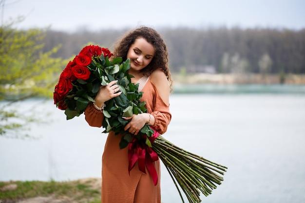 Een mooi meisje van europees uiterlijk met krullend haar en een glimlach op haar gezicht met een enorm boeket rode rozen op een achtergrond van blauw meer. warme zomerdag, gelukkige jonge vrouw, emoties van vreugde
