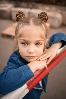 Een mooi meisje van ongeveer zeven jaar oud in een spijkerjasje staat naar de camera te kijken