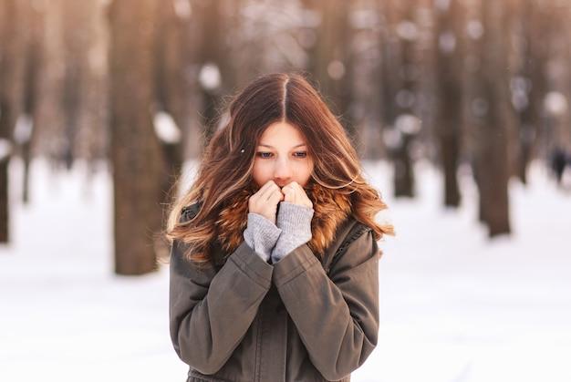 Een mooi meisje verwarmt haar handen in de winter op straat. vorst en zon