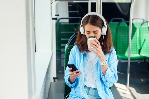 Een mooi meisje zit in de moderne stadstram of metro, luistert naar muziek en drinkt koffie.
