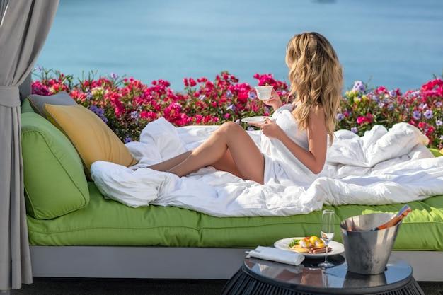 Een mooi meisje zit op de bank van haar hotel en drinkt koffie. ontbijt in de villa