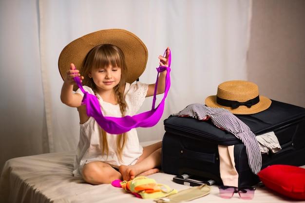 Een mooi meisje zit op het bed en bereidt bagage voor op een reis kleren aanbrengend een koffer dromen van een vakantie