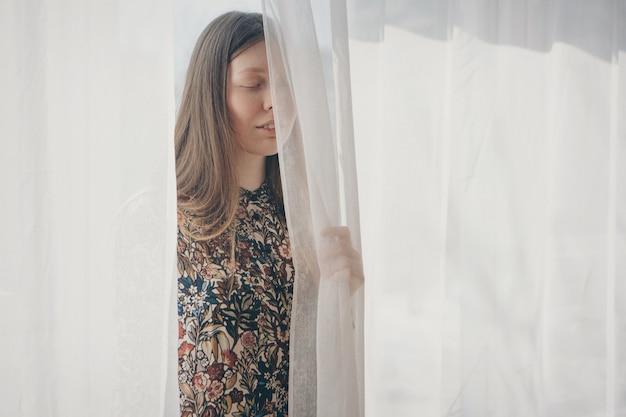 Een mooi meisje zonder make-up kijkt uit van achter het gordijn, een vrouw voor het raam. reclame natuurlijke make-up, ochtend tijdverdrijf