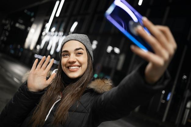 Een mooi meisje zwaait naar de camera van een smartphone