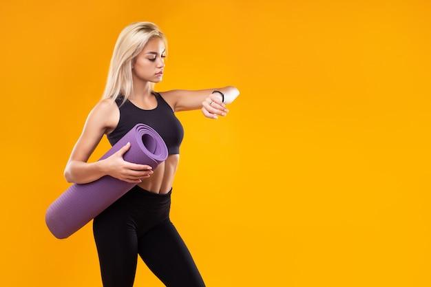 Een mooi model in sportkleding met een slim horloge en een mat in haar handen op een gele achtergrond