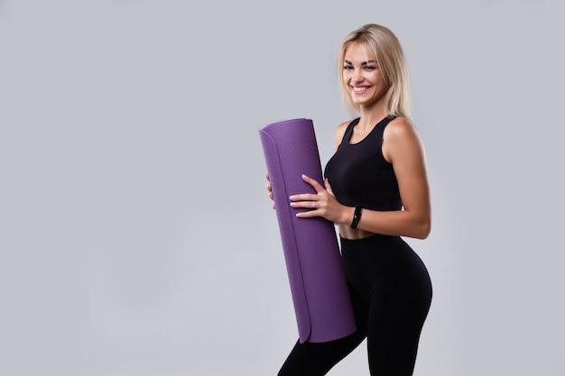 Een mooi model in sportkleding met een slim horloge en een mat in haar handen op een grijze achtergrond