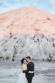 Een mooi paar geliefden in de witte zoutwoestijn, een jonge modelvrouw in de trouwjurk en een knappe brute man in het pak met de witte berg op de achtergrond