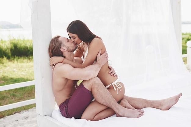 Een mooi paar ontspannen op het zandstrand, het dragen van badkleding. romantische sfeer