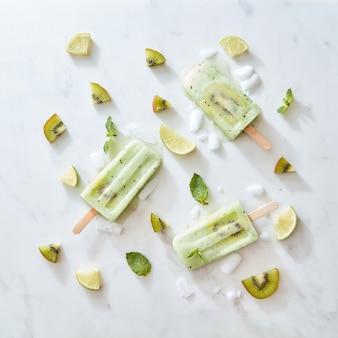 Een mooi patroon van zelfgemaakt gezond ijs op een stokje met plakjes ijs, kiwi, limoen en muntblaadjes op een grijze marmeren achtergrond met ruimte voor tekst. plat leggen