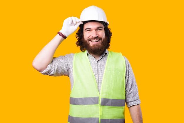 Een mooi portret van een jonge, bebaarde architect die naar de camera glimlacht, houdt zijn witte helm vast bij een gele muur