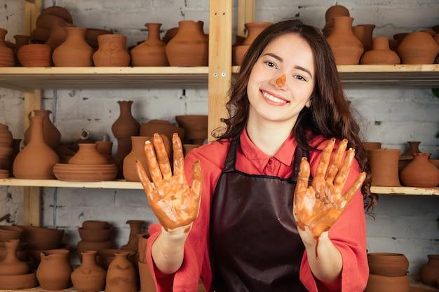 Een mooi pottenbakkersmeisje werkt met klei en maakt een pot met meester. een vrouw werkt met klei op een pottenbakkersschijf. pottenbakker toont zijn handen bevlekt met klei.