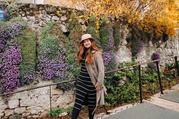 Een mooi romantisch meisje in een jas en hoed loopt door annecy