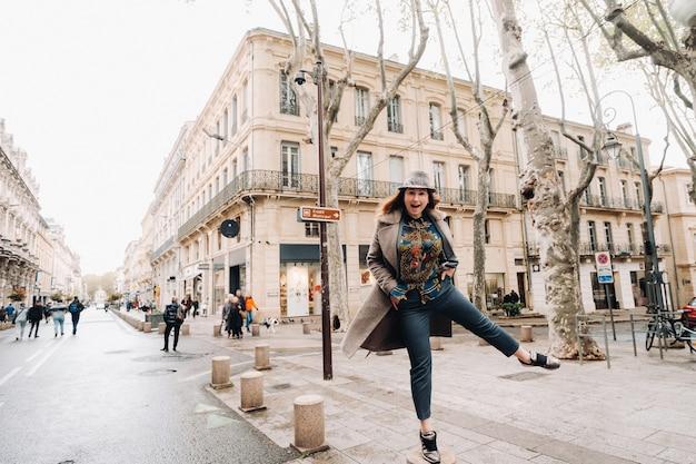 Een mooi romantisch meisje in een jas met haar haren naar beneden rent door de oude stad avignon. frankrijk. meisje in een jas in frankrijk.