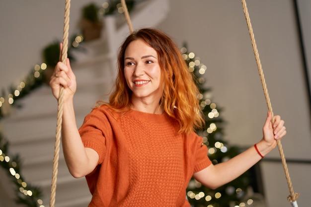 Een mooi roodharig meisje slingert in haar kamer op kerstnacht