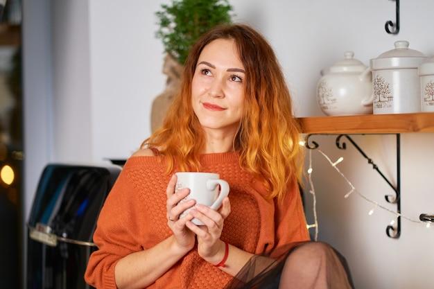 Een mooi roodharig meisje zit op de dakbedekking in een stijlvolle, gezellige keuken