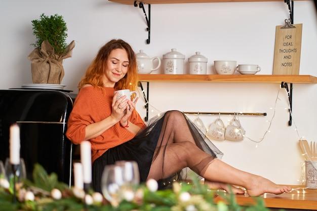 Een mooi roodharig meisje zit op het dakbedekking doek in een stijlvolle gezellige keuken ingericht voor kerstmis