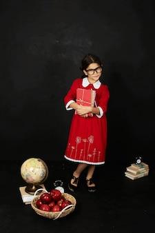 Een mooi schoolmeisje in een rode jurk met een boeken appels en globe op een zwarte achtergrond