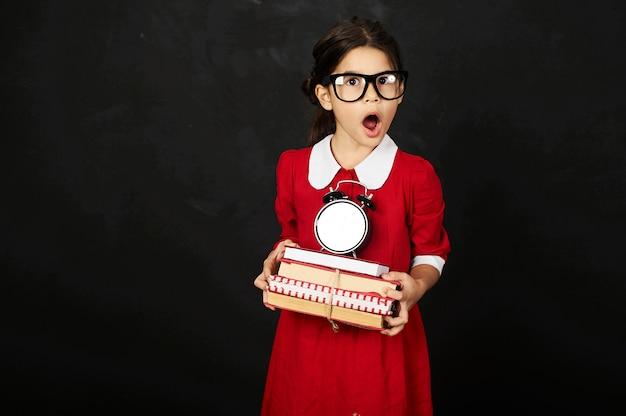 Een mooi schoolmeisje in een rode jurk met een boeken en klok op een zwarte achtergrond