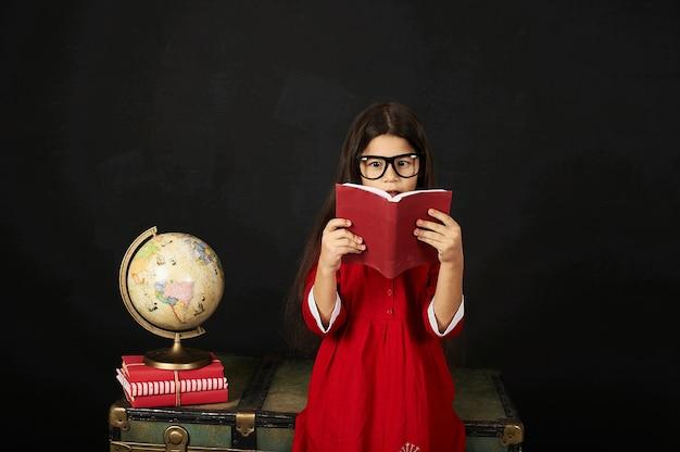 Een mooi schoolmeisje in een rode kleding die een boek op een zwarte achtergrond leest terwijl het zitten op een borst