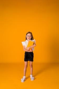 Een mooi schoolmeisje in een uniform en een bril houdt schoolboeken op een gele achtergrond