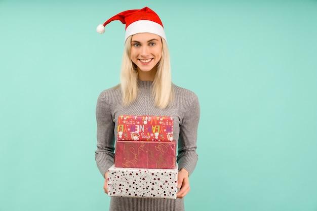 Een mooi sexy meisje in een new year's hoed en grijze jurk, geschenken in handen houden viering van kerstmis of nieuwjaar op blauwe achtergrond