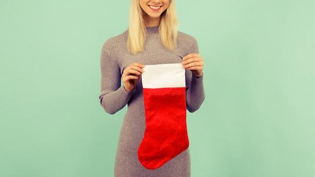 Een mooi sexy meisje in een nieuwjaarshoed en grijze jurk houdt een kerstsok vast. viering van kerstmis of nieuwjaar