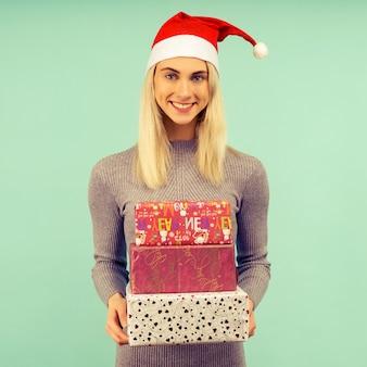 Een mooi sexy meisje in een nieuwjaarshoed en grijze jurk, houdt geschenken in handen. viering van kerstmis of nieuwjaar
