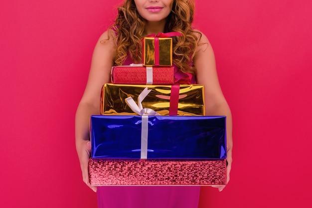 Een mooi sexy meisje in een nieuwjaarshoed, houdt geschenken in handen. viering van kerstmis of nieuwjaar