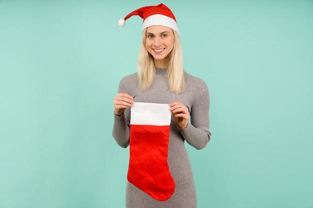 Een mooi sexy meisje in een nieuwjaarsmuts en grijze jurk houdt een kerstsok vast. viering van kerstmis of nieuwjaar - afbeelding