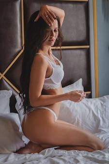 Een mooi slank donkerbruin meisje, zittend op een bed in haar ondergoed in een hotel