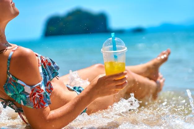 Een mooi slank meisje in een zwembroek geniet van een kleurtje terwijl ze op een tropisch strand ligt