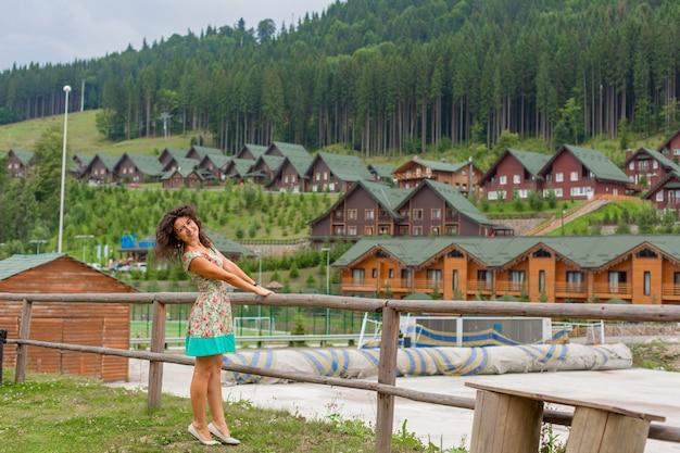 Een mooi slank meisje poseren naast berg skigebied in de zomerdag.