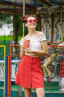 Een mooi slavisch meisje in een rode rok en rode bril in de vorm van lippen met een rood glas met een drankje. ze rust in een pretpark