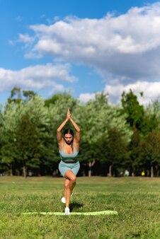Een mooi sportief meisje houdt zich bezig met yoga op groen gras in een stadspark. prapadasana-houding