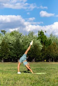 Een mooi sportief meisje in sportkleding beoefent yoga op het groene gras in het stadspark. handstand met touw