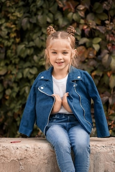 Een mooi stijlvol blond meisje in een blauwe jas zit op een betonnen blok. meisje 7 jaar oud met een glimlach op een achtergrond van bladeren
