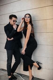 Een mooi, stijlvol paar jonge mensen in zwarte kleding en een bril staat tegen de achtergrond van een kantoorgebouw in de zonsondergang. mode en stijl