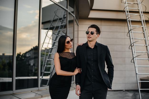 Een mooi, stijlvol paar jonge mensen in zwarte kleding en een bril staat tegen een kantoorgebouw in de zonsondergang. mode en stijl