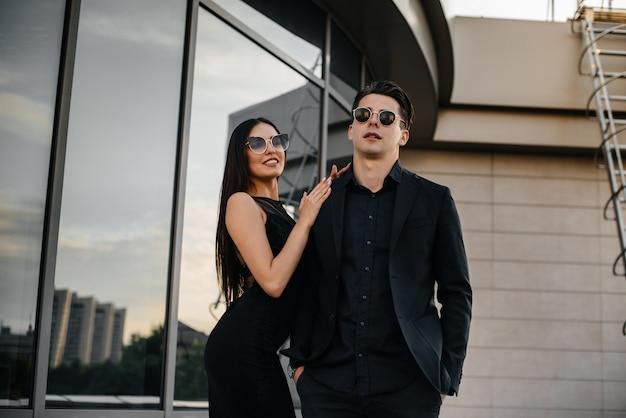 Een mooi, stijlvol paar jonge mensen in zwarte kleding en een bril staat tegen een kantoorgebouw in de zonsondergang. mode en stijl.