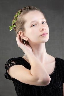 Een mooi tienermeisje met een vlecht met een groen takje van een boom erin geweven op een grijze achtergrond. portret van een geperst meisje met verfijnde trekken.