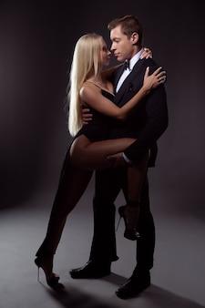 Een mooi verliefd stel omhelst elkaar voor een kus. foto op een donkere achtergrond