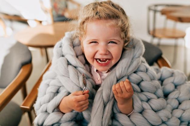 Een mooi, vrolijk meisje in een grijze gebreide plaid lacht vrolijk terwijl ze uitrust in een café
