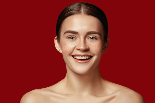 Een mooi vrouwelijk gezicht. perfecte en schone huid van jonge blanke vrouw op rode studio achtergrond.