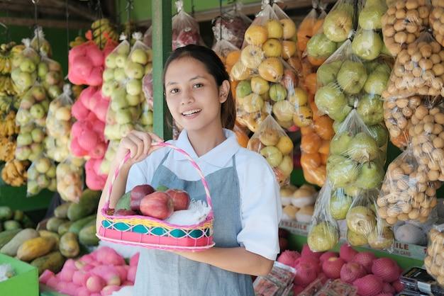 Een mooi winkelmeisje met fruit in een rieten mand voor een fruitpakket