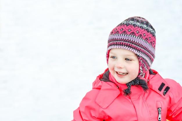 Een mooi wit meisje in een gebreide muts en roze jumpsuit, glimlachend en lachend in de sneeuw.