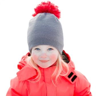 Een mooi wit meisje in een gebreide wintermuts en roze jumpsuit, glimlachend en lachend in de sneeuw. portretclose-up, geïsoleerd