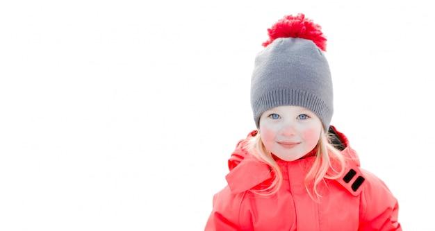 Een mooi wit meisje in een gebreide wintermuts en roze jumpsuit, glimlachend en lachend in de sneeuw