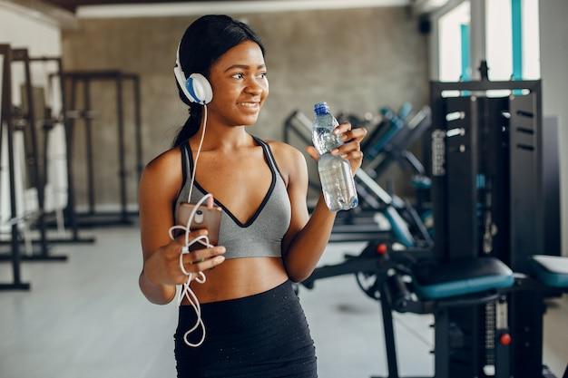 Een mooi zwart meisje is bezig met een sportschool
